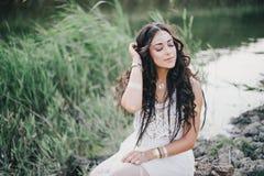 Η όμορφη γυναίκα με τη μακριά σγουρή τρίχα έντυσε στην τοποθέτηση φορεμάτων ύφους boho κοντά στη λίμνη Στοκ Εικόνες