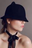 Η όμορφη γυναίκα με τη σκοτεινή τρίχα φορά το κομψό τόξο μαύρων καπέλων και μεταξιού στο λαιμό Στοκ Εικόνες