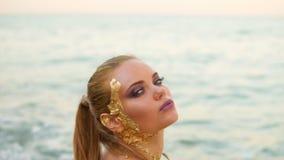 Η όμορφη γυναίκα με το επαγγελματικό χρυσό makeup εξετάζει τη κάμερα και φλερτάρει με το θεατή, σχετικά με την τρίχα της Προκλητι απόθεμα βίντεο