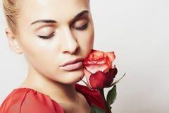 Η όμορφη γυναίκα με το κόκκινο αυξήθηκε κορίτσι και λουλούδι ομορφιάς Λουλούδια Στοκ Φωτογραφία