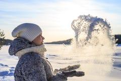 Η όμορφη γυναίκα με το πλεκτά καπέλο και το μαντίλι ρίχνει το χιόνι στην ηλιόλουστη χειμερινή ημέρα στοκ φωτογραφίες με δικαίωμα ελεύθερης χρήσης