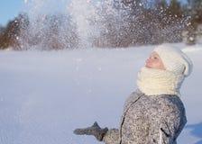Η όμορφη γυναίκα με το πλεκτά καπέλο και το μαντίλι ρίχνει το χιόνι στην ηλιόλουστη χειμερινή ημέρα στοκ φωτογραφία με δικαίωμα ελεύθερης χρήσης