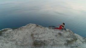 Η όμορφη γυναίκα με το tatoo στην πλάτη κάνει γιόγκας στην κορυφή του βουνού με την άποψη θάλασσας στο ηλιοβασίλεμα _ απόθεμα βίντεο