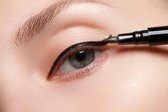 Η όμορφη γυναίκα με φωτεινό αποτελεί το μάτι με το προκλητικό μαύρο σκάφος της γραμμής makeup Μορφή βελών μόδας Κομψή σύνθεση βρα Στοκ Εικόνες