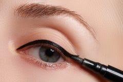 Η όμορφη γυναίκα με φωτεινό αποτελεί το μάτι με το προκλητικό μαύρο σκάφος της γραμμής makeup Μορφή βελών μόδας Κομψή σύνθεση βρα Στοκ εικόνες με δικαίωμα ελεύθερης χρήσης