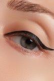 Η όμορφη γυναίκα με φωτεινό αποτελεί το μάτι με το προκλητικό μαύρο σκάφος της γραμμής makeup Μορφή βελών μόδας Κομψή σύνθεση βρα Στοκ εικόνα με δικαίωμα ελεύθερης χρήσης
