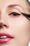 Η όμορφη γυναίκα με φωτεινό αποτελεί το μάτι με το προκλητικό μαύρο σκάφος της γραμμής makeup Μορφή βελών μόδας Κομψή σύνθεση βρα Στοκ Φωτογραφίες