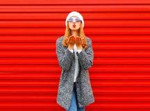 Η όμορφη γυναίκα μόδας που φυσά τα κόκκινα χείλια στέλνει ένα φιλί αέρα Στοκ Φωτογραφία