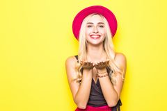 Η όμορφη γυναίκα μόδας στέλνει στον αέρα το γλυκό φιλί που φορά ένα κόκκινο καπέλο και κίτρινα ενδύματα χρώματος πέρα από το ζωηρ Στοκ εικόνες με δικαίωμα ελεύθερης χρήσης