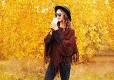 Η όμορφη γυναίκα μόδας με το φλυτζάνι καφέ που φορούν τα γυαλιά ηλίου μαύρων καπέλων και το φθινόπωρο έπλεξε poncho πέρα από τα κ Στοκ Εικόνες