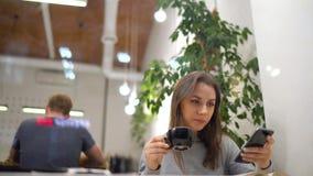 Η όμορφη γυναίκα ξοδεύει το χρόνο της σε έναν καφέ: χρησιμοποιώντας το smartphone και πίνοντας τον καφέ απόθεμα βίντεο