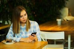 Η όμορφη γυναίκα πίνει τον καφέ και διαβάζει τις ειδήσεις πρωινού Στοκ Εικόνες