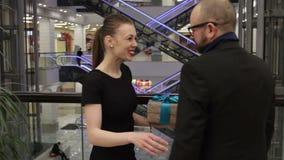 Η όμορφη γυναίκα παίρνει το παρόν από έναν άνδρα στο μαύρο σακάκι απόθεμα βίντεο