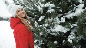 Η όμορφη γυναίκα περπατά χαρωπά στα κωνοφόρα δέντρα που καλύπτονται από το χιόνι απόθεμα βίντεο