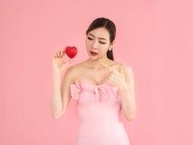 Η όμορφη γυναίκα που κρατά τη μίνι καρδιά, προκλητικό κορίτσι παρουσιάζει δάχτυλα στοκ εικόνες