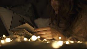 Η όμορφη γυναίκα προκαλεί τις μνήμες από το λεύκωμα φωτογραφιών μπροστά από τα φω'τα Χριστουγέννων απόθεμα βίντεο