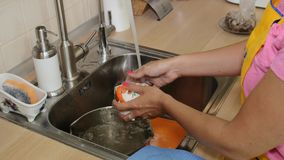 Η όμορφη γυναίκα πλένει τα πιάτα στο νεροχύτη κουζινών φιλμ μικρού μήκους