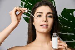 Η όμορφη γυναίκα ρίχνει ένα κρύσταλλο - σαφές καλλυντικό για το δέρμα από το σιφώνιο στο πρόσωπό της και αισθάνεται τη φρεσκάδα κ στοκ εικόνα