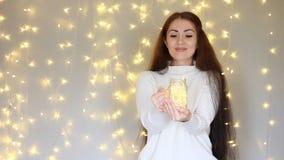 Η όμορφη γυναίκα σε ένα άσπρο πουλόβερ κρατά στα χέρια που ένας λαμπτήρας, κλείνει τα μάτια του και να ονειρευτεί στο υπόβαθρο τω απόθεμα βίντεο
