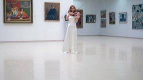 Η όμορφη γυναίκα σε ένα άσπρο φόρεμα παίζει το βιολί στη στοά απόθεμα βίντεο