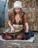 Η όμορφη γυναίκα σε ένα αγροτικό φόρεμα κάθεται σε έναν σανό και κοσκινίζει το σιτάρι στοκ εικόνες με δικαίωμα ελεύθερης χρήσης