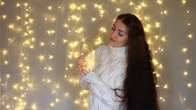 Η όμορφη γυναίκα σε ένα θερμό άσπρο πουλόβερ κρατά στα χέρια που ένας λαμπτήρας, κλείνει τα μάτια και να ονειρευτεί του απόθεμα βίντεο