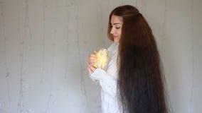 Η όμορφη γυναίκα σε ένα θερμό άσπρο πουλόβερ κρατά στα χέρια που ένας λαμπτήρας, κλείνει τα μάτια του και να ονειρευτεί στο υπόβα φιλμ μικρού μήκους
