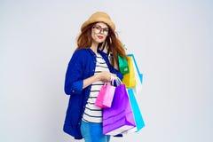 Η όμορφη γυναίκα σε ένα καπέλο και τη φθορά των γυαλιών σε ένα ελαφρύ υπόβαθρο κρατά πολλές συσκευασίες, αγορές, ένας shopaholic Στοκ Εικόνες