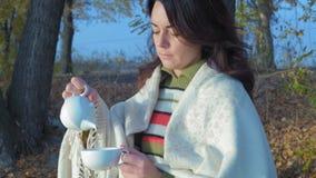 Η όμορφη γυναίκα σε ένα καρό χύνει το πράσινο τσάι από μια Teapot πορσελάνης συνεδρίαση σε έναν πάγκο νωρίς το πρωί απόθεμα βίντεο