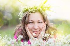 Η όμορφη γυναίκα σε ένα στεφάνι από τα λουλούδια στις ακτίνες ήλιων Στοκ φωτογραφία με δικαίωμα ελεύθερης χρήσης