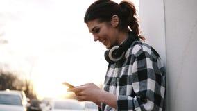 Η όμορφη γυναίκα στέκεται κοντά στην άσπρη στήλη, το κράτημα κινητός στα χέρια της και τη δακτυλογράφηση Ακουστικά Ο ήλιος λάμπει απόθεμα βίντεο