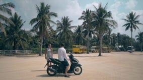 Η όμορφη γυναίκα στέκεται κοντά στη συνεδρίαση τύπων στη θαυμάσια μοτοσικλέτα φιλμ μικρού μήκους