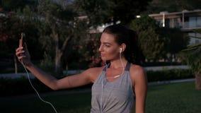 Η όμορφη γυναίκα στα ακουστικά πυροβολεί selfie στο τηλέφωνο το καλοκαίρι απόθεμα βίντεο