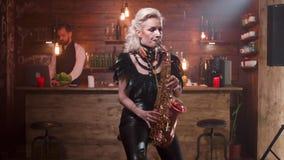 Η όμορφη γυναίκα στα προκλητικά μαύρα ενδύματα δέρματος παίζει ένα τραγούδι σε ένα saxophone φιλμ μικρού μήκους