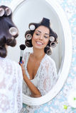 Η όμορφη γυναίκα στα ρόλερ τρίχας βάζει στο πρωί makeup Στοκ Εικόνα