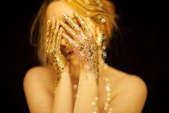 Η όμορφη γυναίκα στα χρυσά, χρυσά χέρια, ακτινοβολεί αισθησιακή πολυτέλεια γοητείας Στοκ Εικόνα