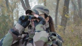 Η όμορφη γυναίκα στην κάλυψη στρατού κοιτάζει μέσω του ομιχλώδους πρωινού διοπτρών μακριά απόθεμα βίντεο