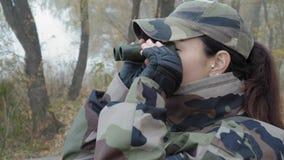 Η όμορφη γυναίκα στην κάλυψη στρατού κοιτάζει μέσω των διοπτρών μακριά στον ποταμό στην ομίχλη σε ένα κρύο πρωί απόθεμα βίντεο