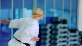 Η όμορφη γυναίκα στο άσπρο κιμονό παρουσιάζει karate τέχνασμα από τον πίσω φιλμ μικρού μήκους