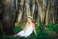 Η όμορφη γυναίκα στο άσπρο φόρεμα κάθεται στη χλόη στη μέση ενός θερινού δάσους Στοκ Εικόνες