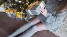 Η όμορφη γυναίκα στο γκρίζο πουλόβερ διακοσμεί παρουσιάζει το κιβώτιο και το βάζει κάτω από το χριστουγεννιάτικο δέντρο, λαμπρό χ φιλμ μικρού μήκους