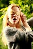 Η όμορφη γυναίκα στο ηλιόλουστο δάσος, κάλυψε το πρόσωπό της με την τρίχα, στοκ φωτογραφίες με δικαίωμα ελεύθερης χρήσης