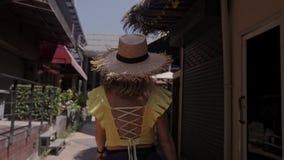 Η όμορφη γυναίκα στο καπέλο αχύρου περπατά την οδό Παιχνίδι στη κάμερα απόθεμα βίντεο