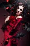 Η όμορφη γυναίκα στο κόκκινο ύφασμα με το κόκκινο αυξήθηκε και πεταλούδες Στοκ Εικόνες