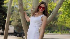 Η όμορφη γυναίκα στο πάρκο πόλεων κάνει το φιλί αέρα απόθεμα βίντεο