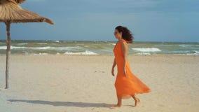 Η όμορφη γυναίκα στο πορτοκαλιά φόρεμα και τα γυαλιά ηλίου πηγαίνει στην αμμώδη παραλία στο θυελλώδη καιρό με τα γυμνά πόδια φιλμ μικρού μήκους