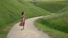 Η όμορφη γυναίκα στο φόρεμα κοιτάζει γύρω από και περίπατος στην πορεία αμμοχάλικου απόθεμα βίντεο
