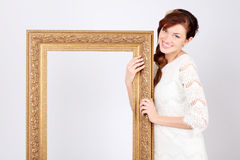 Η όμορφη γυναίκα στο φόρεμα κρατά το μεγάλο επιχρυσωμένο πλαίσιο. Στοκ Εικόνες