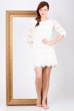 Η όμορφη γυναίκα στο φόρεμα στέκεται κοντά στο πλαίσιο Στοκ Εικόνες