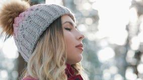 Η όμορφη γυναίκα στο χειμερινό καπέλο απολαμβάνει το χιόνι και αναπνέει τη βαθιά στάση έξω στο χιόνι στο δασικό πορτρέτο απόθεμα βίντεο